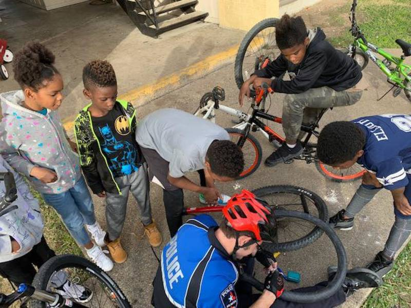 Police Officers Help Children Repair Flat Bicycle Tires